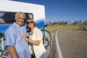 Couple standing behind their newly financed caravan with a bicycle rack on the back